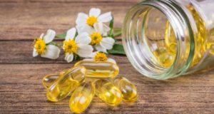 e-vitamini kapsülleri ve papatyalar
